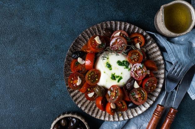 어두운 배경에 얇게 썬 토마토, 모짜렐라 치즈, 올리브 오일을 곁들인 이탈리아 카프레제 샐러드. 평면도. 부라타와 마늘을 곁들인 블랙 토마토 샐러드. 컴포트 푸드. 지속 가능한 소비.