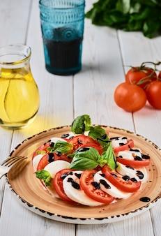 Итальянский салат капрезе с помидорами, сыром моцарелла, базиликовым бальзамическим уксусом и оливковым маслом. на керамической тарелке на белом деревянном столе. стиль кантри. вегетарианское блюдо