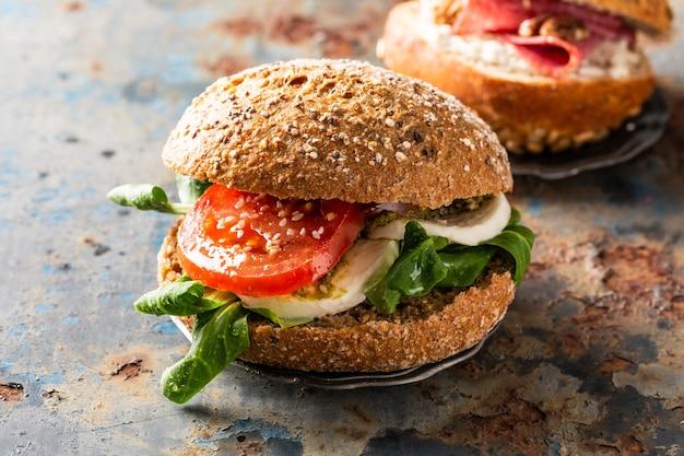 Итальянские сэндвичи капрезе со свежими помидорами, сыром моцарелла и салатом из баранины, мультизерновая булочка