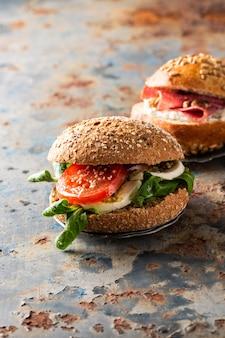 Italian caprese sandwiches with fresh tomatoes, mozzarella cheese and lamb's lettuce, multigrain bun
