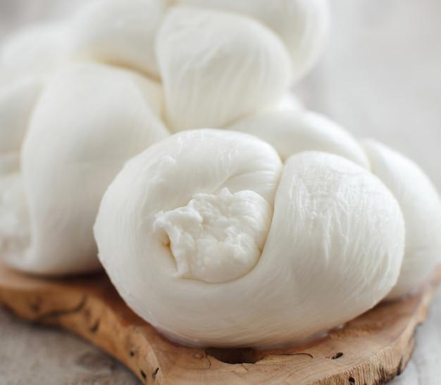 木の板にイタリアのチーズ編みモッツァレラチーズをクローズアップ
