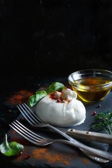 Итальянский сыр буррата, зелень и оливковое масло на темной поверхности