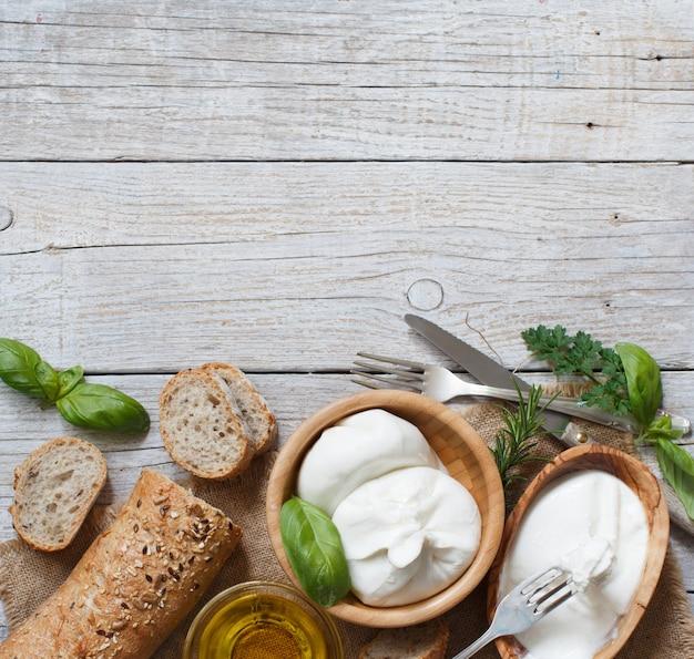 Итальянский сыр буррата, оливковое масло и вид сверху хлеба