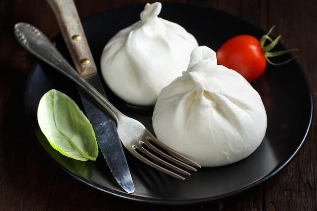 Итальянский сыр буррата на тарелке на темном фоне