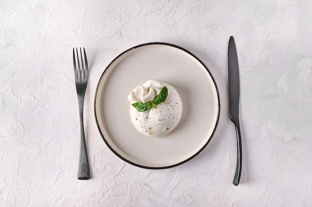 Итальянский сыр буррата с базиликом на белой тарелке с черной вилкой и ножом, вид сверху, копия пространства