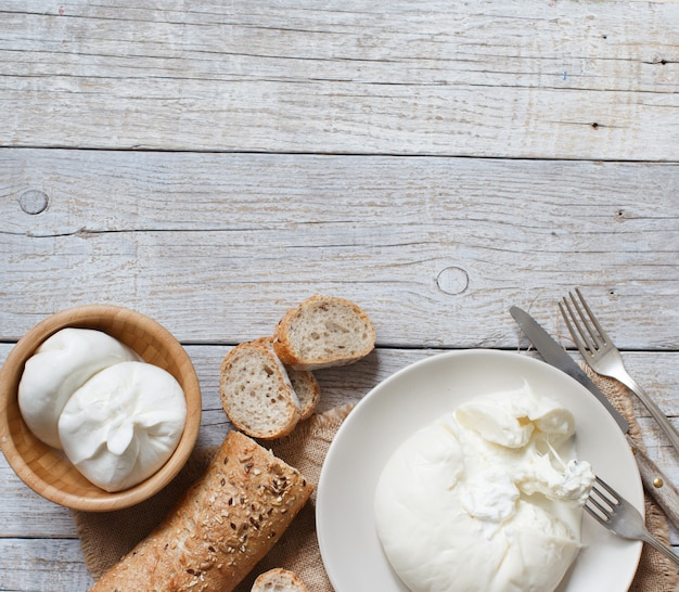 Итальянский сыр буррата с хлебом на деревянной поверхности