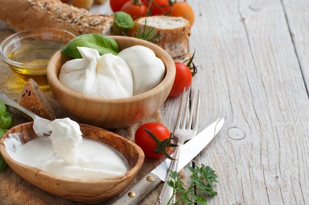 Итальянский сыр буррата с хлебом, овощами и зеленью