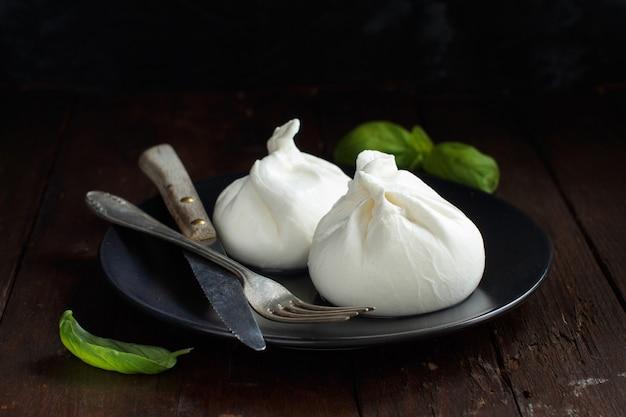 Итальянский сыр буррата с вилкой и ножом на темной поверхности Premium Фотографии