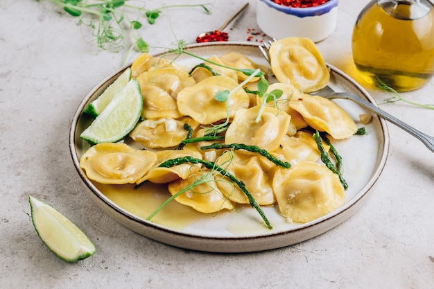 허브 레몬 버터 소스에 구운 아스파라거스를 곁들인 이탈리아 치즈 라비올리
