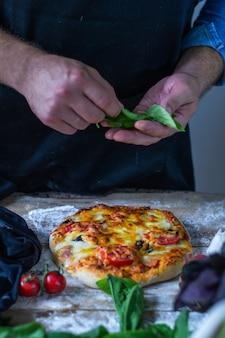 イタリア人シェフがピザを調理する男の手がピザ生地を調理するピザシェフの手