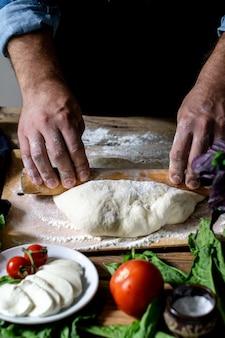 イタリア人シェフがピザを調理する男の手がピザ生地を調理する