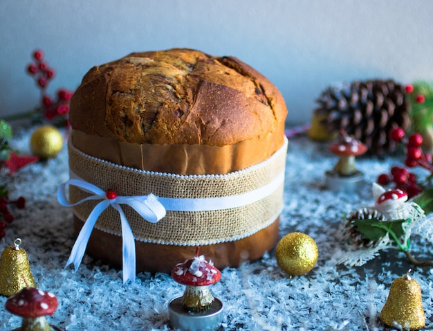 Italian chocolate panettone christmas cake with bauble decorations candlespine cones on a wooden background.