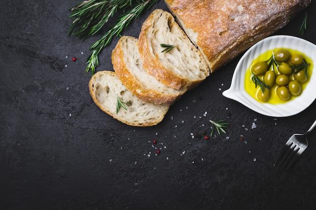 Итальянский хлеб чиабатта, нарезанный ломтиками с зеленью и оливками на черном фоне.