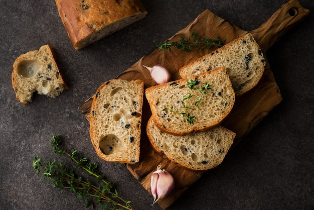 Italian ciabatta bread with olives and herbs, top view