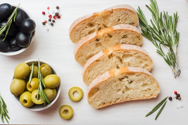 Italian ciabatta bread with olives and rosemary on a cutting board