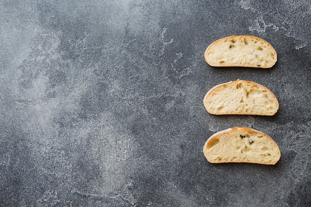 Italian ciabatta bread with olives and rosemary on a dark concrete background