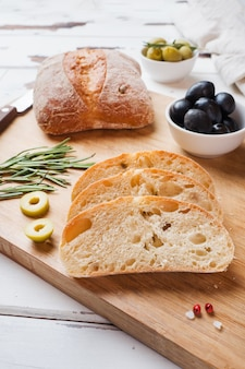 Italian ciabatta bread with olives and rosemary on a wooden board