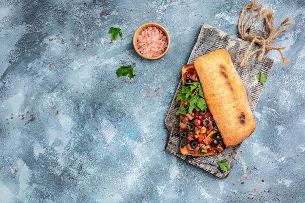 刻んだトマト野菜、ハーブ、オイルをグリルまたはトーストした無愛想なバゲットに添えたイタリアンチャバタ。イタリアのブルスケッタ。バナー、メニュー、テキストのレシピの場所、上面図。