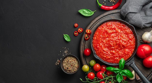검은 배경에 바질과 후추를 곁들인 이탈리아 고전 홈메이드 소스. 마리나라 소스. 파스타, 피자 드레싱.