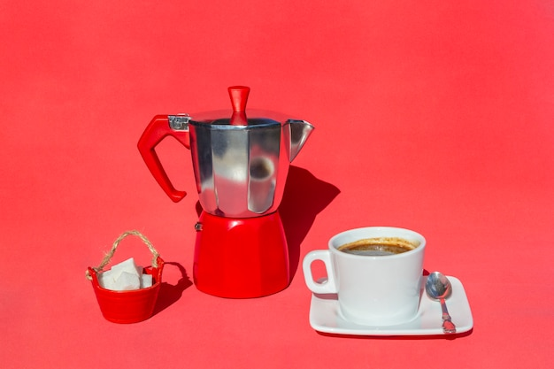 Italian coffee maker, cup and saucer of hot drink
