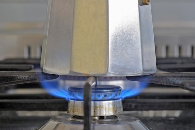 Итальянская кофеварка на плите с зажженным огнем, готова к подаче