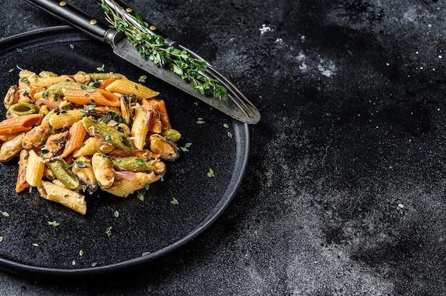 ムール貝を皿に盛ったイタリアンカラーのペンネパスタ。黒の背景。上面図。スペースをコピーします。