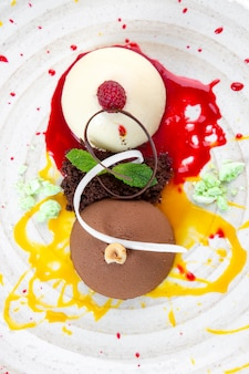 Итальянские разноцветные шарики мороженого семифреддо с шоколадом и малиной на белой тарелке