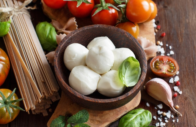 Italian cooking ingredients mozzarella, pasta, tomatoes, garlic, herbs and other close up