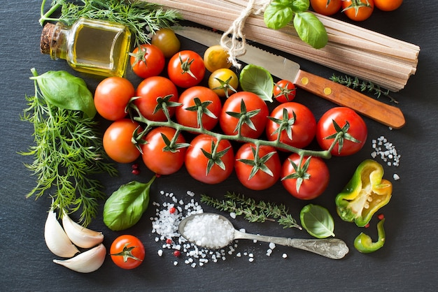 Italian cooking ingridients : cherry tomatoes, herbs, pasta and olive oil on a dark background