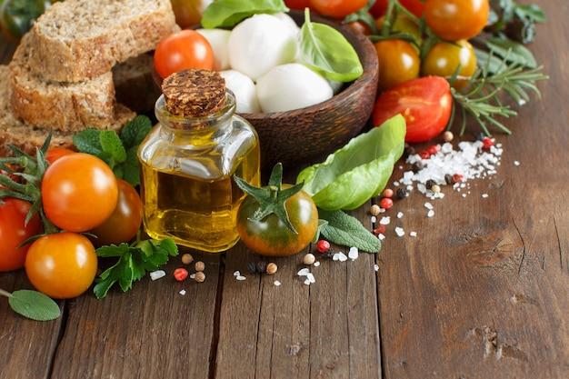 Ингредиенты для итальянской кухни: моцарелла, помидоры, базилик, оливковое масло и хлеб.