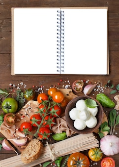 イタリア料理の材料モッツァレラチーズ、トマト、ニンニク、ハーブ、オリーブオイル、その他の上面図