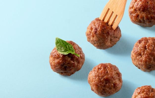青い背景にバジルの葉と木製のフォークでイタリア料理ビーフミートボール。メニュー、レシピ、またはパッキングのテンプレート