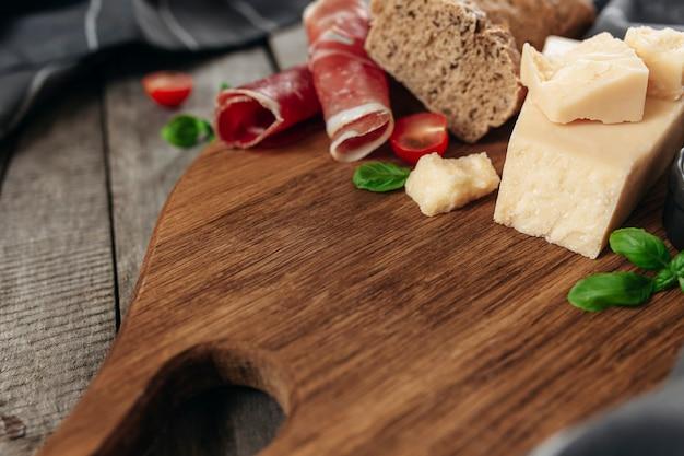 イタリア料理のコンセプト。まな板、パルメザンチーズのチャンク、薄くスライスしたハム、新鮮なチェリートマトのカット、バジルの葉の枝、無愛想なパンのトースト、木製テーブルのキッチンタオル