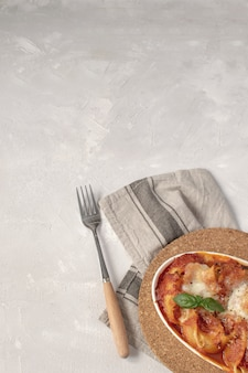 Italian cuisine flat lay - baked pasta with tomato and mozzarella sauce.