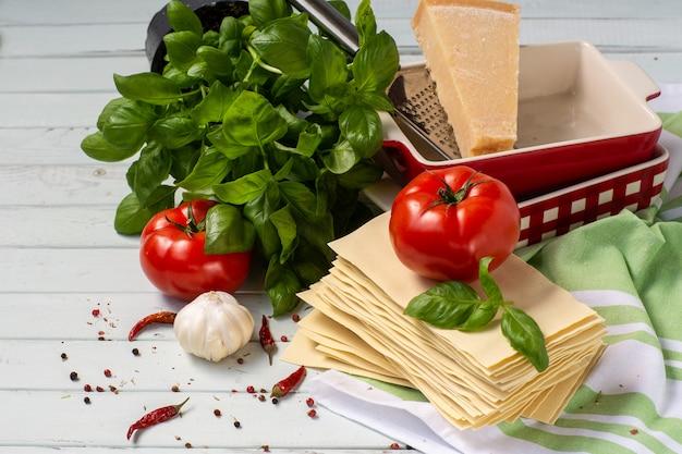 Итальянская кухня-лазанья. продукты для лазаньи помидоры, базилик, тесто, формы для выпечки.
