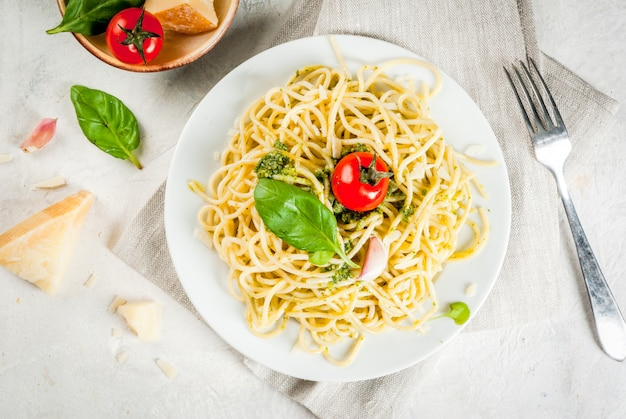 Italian cuisine lunch or dinner for one pesto pasta spaghetti with pesto basil leaves garlic parmesan cheese and cherry tomatoes one portion on a white stone table