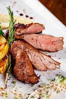 이탈리아 요리. 돼지 고기 안심 스테이크, 감자 반찬, 데미 글라스 소스. 흰 접시에 봉사하는 아름다운 레스토랑