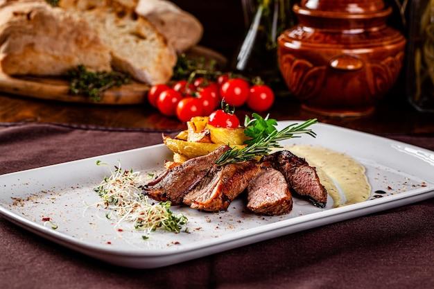 Italian cuisine. pork tenderloin steak, side dish of potatoes and demi glace sauce. beautiful restaurant serving in a white plate