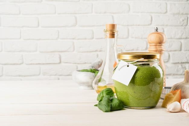 이탈리아 요리. 홈메이드 이탈리안 페스토 소스를 준비합니다. 빈 태그가 있는 유리병에 든 홈메이드 페스토 소스, 조롱 디자인