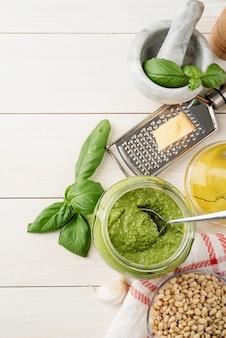 이탈리아 요리. 홈메이드 이탈리안 페스토 소스를 준비합니다. 재료가 든 유리 항아리에 홈메이드 페스토 소스, 흰색 나무 탁자 위에 평평한 평면도, 복사 공간