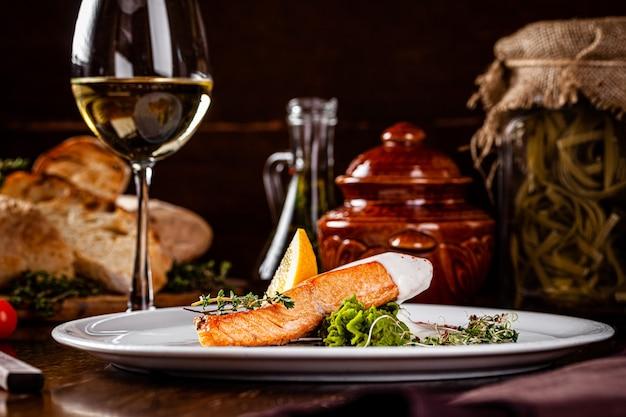 イタリア料理。赤魚ステーキ、サーモンとレモン、ほうれん草のおかず。白ワインと白皿で提供する美しいレストラン