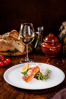 Italian cuisine. red fish steak, salmon with lemon, a side dish of spinach. beautiful restaurant serving in a white plate with a glass of white wine