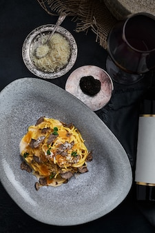 Italian cuisine  spaghetti with black truffle on a gray plate and bottle of wine