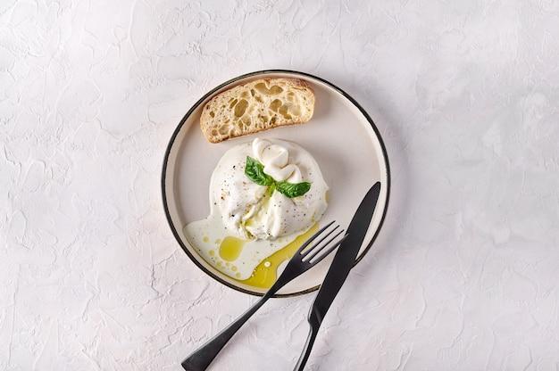 Итальянский нарезанный сыр буррата с хлебом чиабатта и оливковым маслом на белой тарелке с черным ножом и