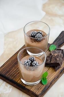 Итальянский десерт - шоколадная панакота, мусс, крем или пудинг с ежевикой в стакане на доске на светлом бетонном фоне. вертикальная ориентация. скопируйте пространство.