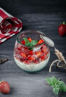 Italian dessert panna cotta with fresh strawberries and mint in a glass jar on dark wood background