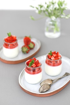 Italian dessert panna cotta with fruit jelly and fresh pieces of strawberries on gray