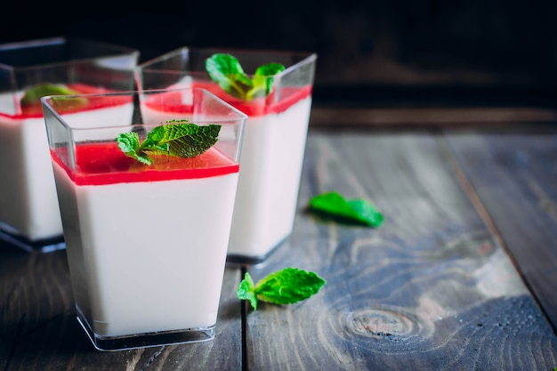 Italian dessert panna cotta with raspberry sauce served for three in small transparent glasses