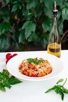 白いテーブルの上にソースとイタリア料理ミートボールスパゲッティパスタ