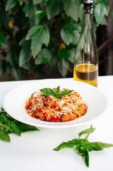 白いテーブルの上に酢とイタリア料理ミートボールスパゲッティパスタ